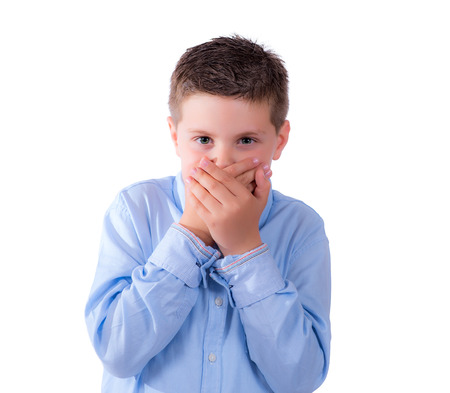photographic portrait of a nine year old boy covering his mouth on a white background Standard-Bild