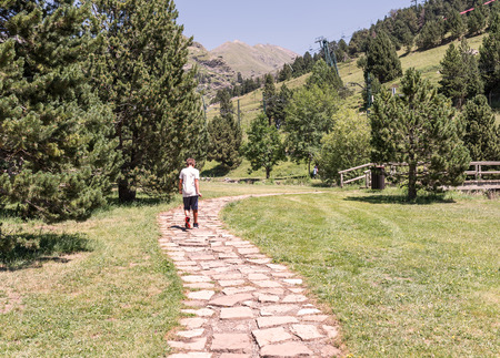 walking trail: Child walking along a path between mountains