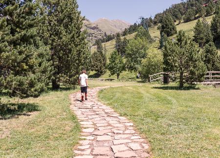 niños caminando: Niño que recorre a lo largo de un camino entre montañas