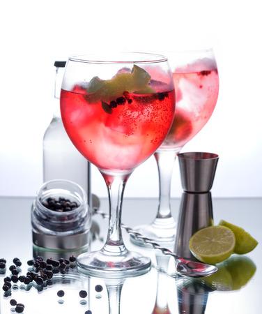 coctel de frutas: Fotografías de un gin tonic con frutos rojos y vidrio aisladas sobre fondo blanco
