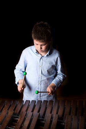 xylophone: Boy playing on xylophone. Black background, close-up