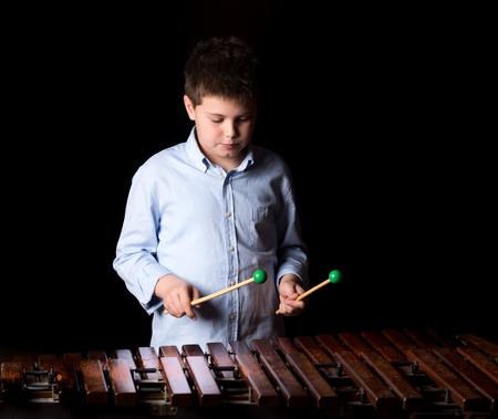 xilofono: Muchacho que juega en el xil�fono. fondo negro, primer plano Foto de archivo