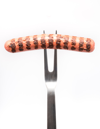 Grilled sausage pricked on fork. White background