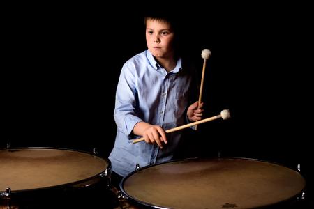 bass drum: Little drummer with drumsticks on black background
