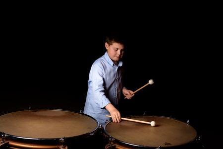 Little drummer with drumsticks on black background