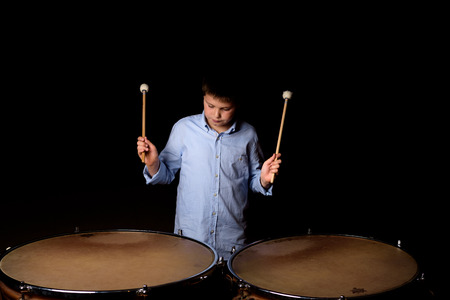 Little drummer with drumsticks on black background photo