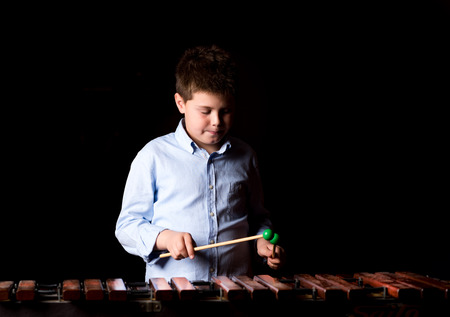 down beat: Boy playing on xylophone. Black background, close-up