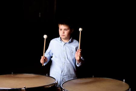down beat: Little drummer with drumsticks on black background