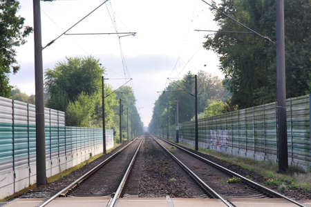 Railway tracks with noise protection walls and trees at the side