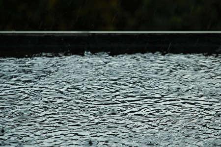 Rain is makes circles on a black flat roof
