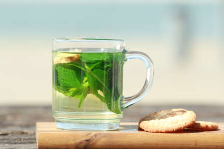 Peppermint tea with green leaves and cookies in front of a beach