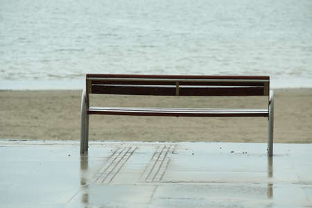 Wooden bench in front of the beach and the ocean on a rainy day