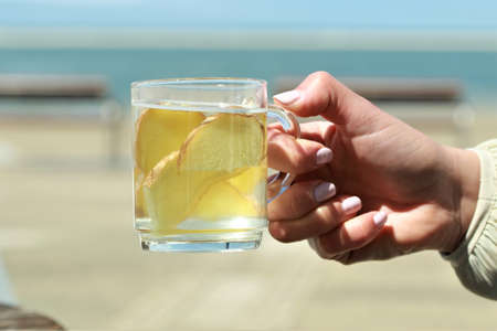 Ginger tea with slices of ginger hold by a hand in front of a beach
