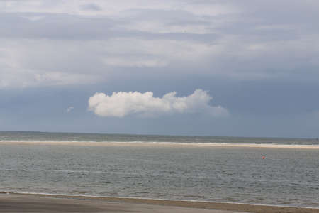 One white cloud at the blue sky above the sea