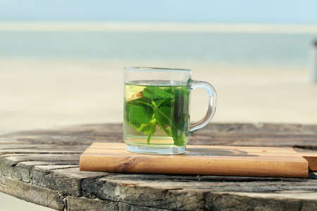 Peppermint tea with green leaves in front of a beach