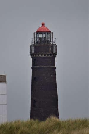 A brick lighthouse against a gray sky