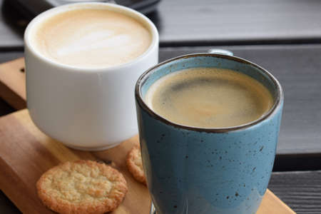 Two cups of coffee and a cookie as a close up