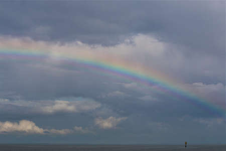 Rainbow above the north sea against a blue sky with clouds