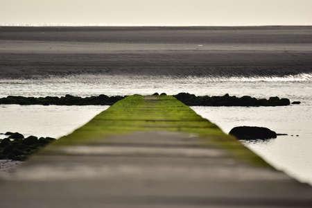 Stone pier by the sea overgrown with green algae and a sandbank Banco de Imagens