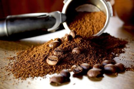 café molido y habas en el fondo de madera