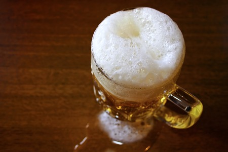 froth: Mug full of beer with froth on the wooden table Stock Photo