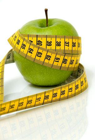 apple in measuring tape over a white background