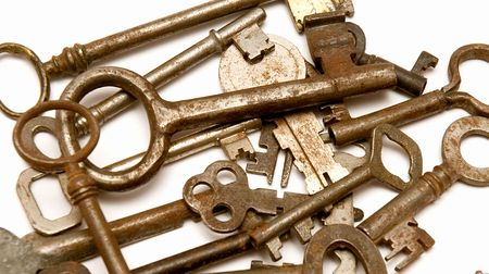 several vintage keys against a white background