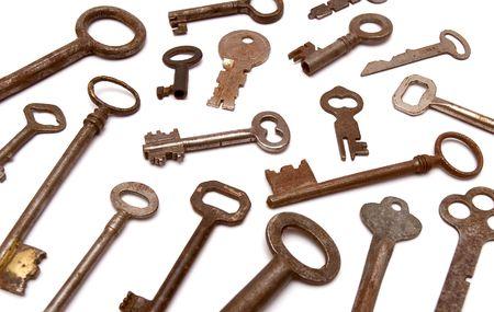 several vintage keys against a white background