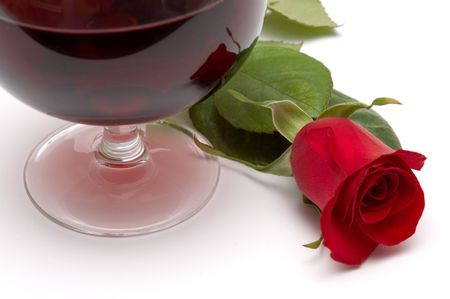 beautiful red rose reflection on a red wine glass photo