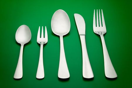arrangement of table silverware over green background Stock Photo