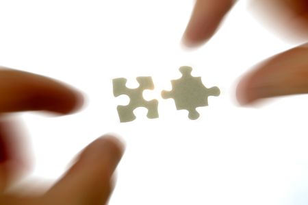 hands approaching two puzzle pieces with radial blur photo