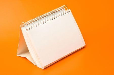 blank spiral calendar over an orange background Stock Photo