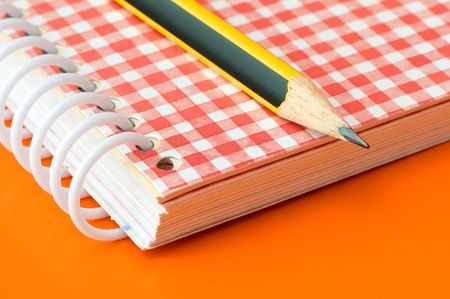 pencil and notebook over an orange background Stock Photo - 3595861