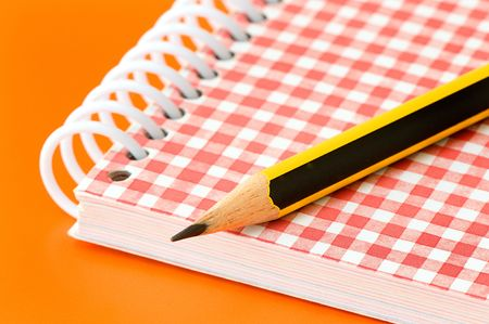 pencil and notebook over an orange background Stock Photo - 3595862