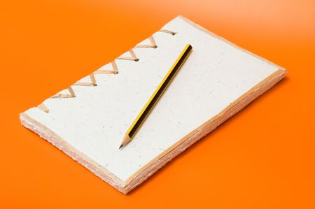 recycled notepad and pencil over an orange background Stock Photo - 3595851