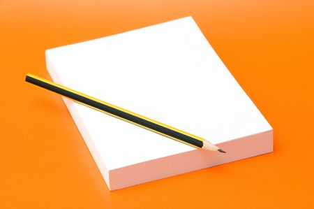 blank book and pencil over an orange background photo