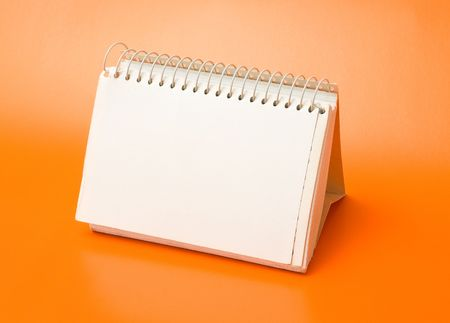school aged: blank spiral calendar over an orange background Stock Photo