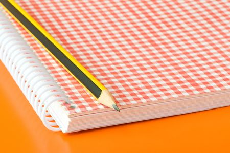 pencil and notebook over an orange background Stock Photo - 3680951