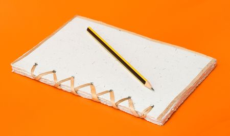 recycled notepad and pencil over an orange background photo