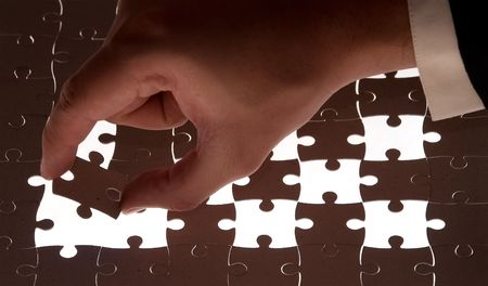 puzzle and businessman hand holding a piece