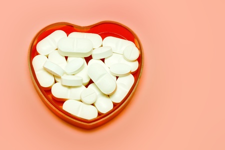 plastic heart: plastic heart holding some pills over pink