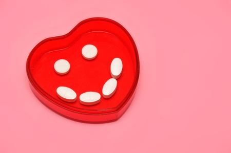 plastic heart holding some pills over pink Stock Photo - 8344434