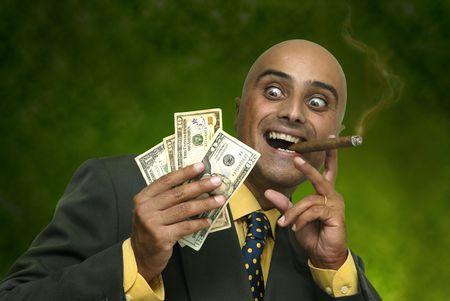 Uomo d'affari con i soldi isolato nei confronti di un verde scuro di sfondo