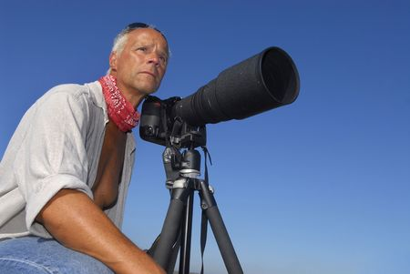 admiring: Adventure photographer posing with is camera outdoors
