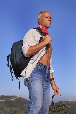 aventurero: Apuesto hombre maduro aventurero posando al aire libre con una mochila Foto de archivo