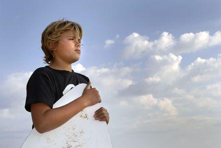 skimming: Boy posing in the beach with a skim-board