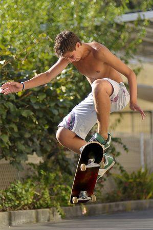Chico con patineta saltar en el aire Foto de archivo - 4930800
