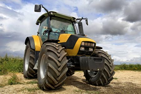 agricultural equipment: Tractor in the field with a cloudy sky