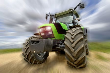 Green tractor in the field with a cloudy sky Stock Photo - 4966910
