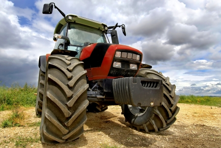 agricultural equipment: Red tractor in the field with a cloudy sky